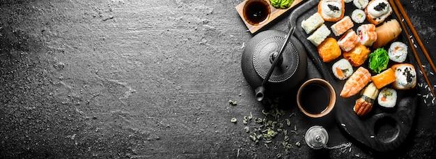 Суши, роллы и маки с соевым соусом, имбирем и зеленым чаем на черном деревенском столе