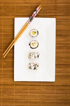 Sushi rolls arranged in a row on white place with wooden chopsticks over placemat