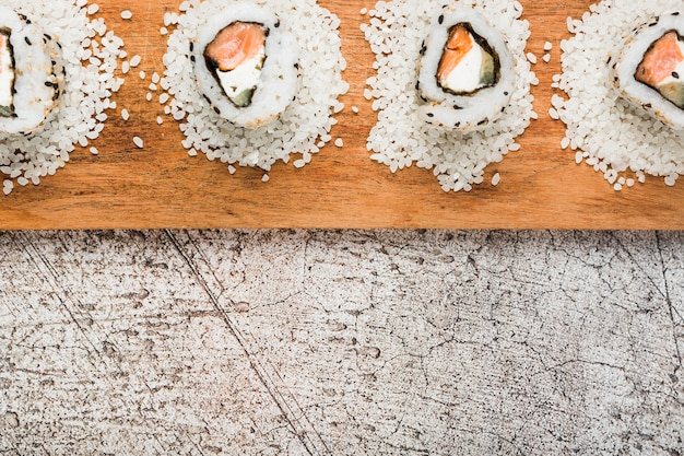 Sushi rolls arranged on uncooked rice over the wooden tray
