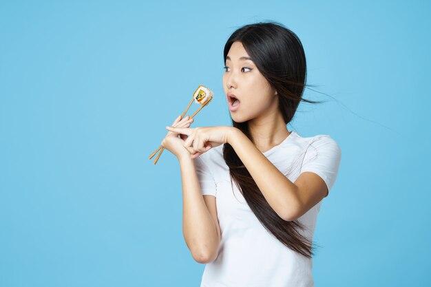 寿司を食べる白いtシャツでアジアの外観の女性を食べる箸を食べ物を食べる