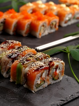 Sushi rolls on colored plates on a black background
