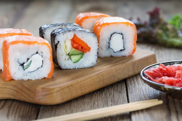 Sushi rolls on a cutting board with ginger and herbs. natural wooden