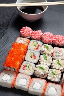 Sushi rolls on a dark stone background with bamboo sticks and soy sauce
