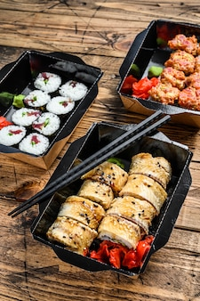 The sushi rolls in the delivery package, ordered in sushi take-out restaurant.