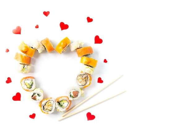Суши-роллы на день святого валентина в форме сердца на белом фоне.