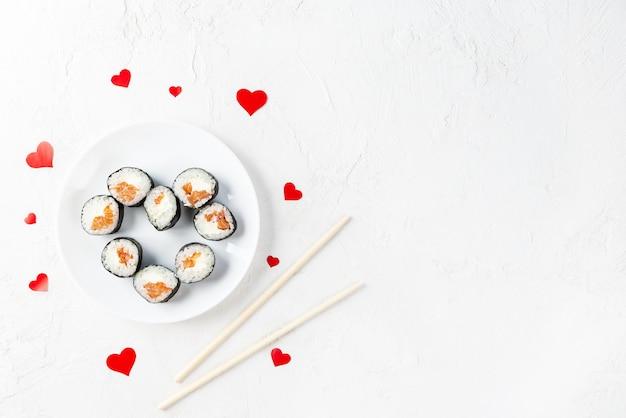 白い皿に赤いハートが付いたバレンタインデーの巻き寿司。