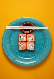 Sushi rolls in green plate on yellow background with bamboo sticks and soy sauce