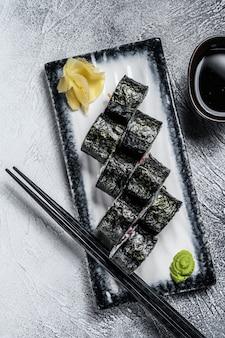 Суши роллы с хосомаки с лососем, авокадо и тунцом. серый фон вид сверху