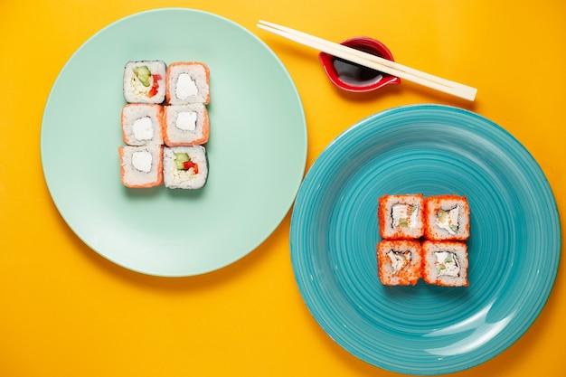 Суши-роллы в зеленой тарелке на желтом фоне с бамбуковыми палочками и соевым соусом