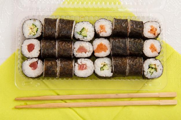 寿司は、ナプキンに木の棒が付いたプラスチックの箱にアボカドと赤い魚が入った海苔シートで巻かれています。上面図。包装食品の配達。