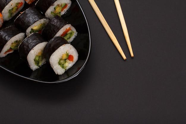 セラミックプレートと木の棒にアボカドと赤魚を乗せた海苔巻き寿司。黒の背景を持つ上面図。