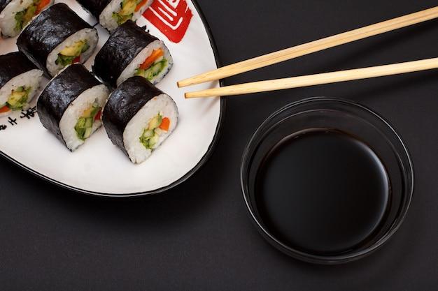 セラミックプレートにアボカドと赤魚を乗せた海苔巻き寿司。醤油と木の棒でボウル。黒の背景を持つ上面図。