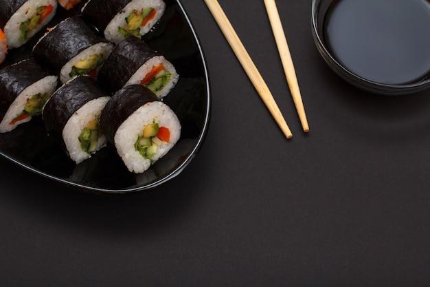 Суши-роллы в листах из водорослей нори с авокадо и красной рыбой на керамической тарелке. чаша с соевым соусом и деревянными палочками. вид сверху с черным фоном.