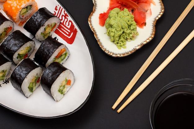 セラミックプレートにアボカドと赤魚を乗せた海苔巻き寿司。赤生姜の酢漬けとわさびの盛り合わせ。醤油と木の棒でボウル。上面図。
