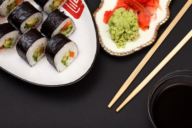 Суши-роллы в листах из водорослей нори с авокадо и красной рыбой на керамической тарелке. тарелка с красным маринованным имбирем и васаби. чаша с соевым соусом и деревянными палочками. вид сверху.