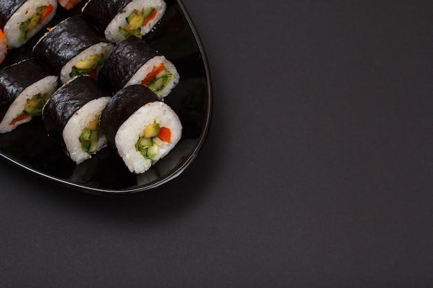 セラミックプレートにアボカドと赤魚を乗せた海苔巻き寿司。黒の背景とコピースペースの上面図。