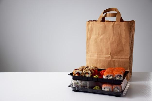 Суши-роллы в пластиковой коробке возле бумажного пакета на белом столе. доставка или забрать понятие.