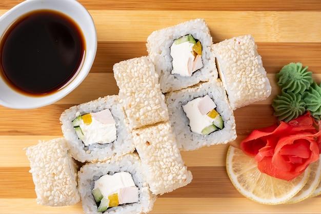 Суши, роллы в белом кунжуте, с сыром, авокадо и креветками. на доске. на красном фоне. для любых целей.