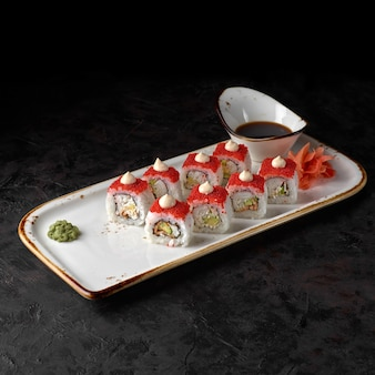 스시는 쌀, 장어, 대게, 아보카도, 핫 소스, 토비코 캐비어를 곁들인 가와사키 마키를 롤링합니다.