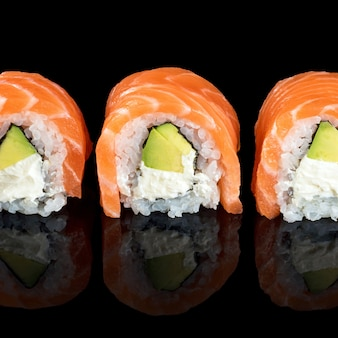 Sushi rolls made of fresh raw salmon, cream cheese and avocado isolated on black with reflections