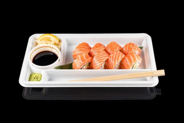 Суши-роллы из свежего сырого лосося, сливочного сыра и авокадо в белом пластиковом контейнере, готовые к употреблению на черном фоне с отражениями