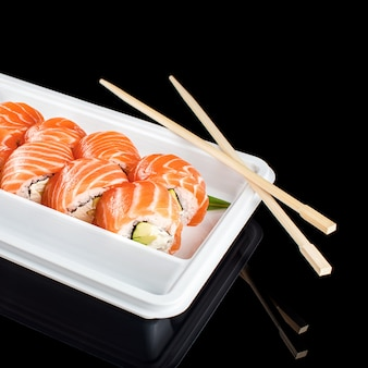 Суши-роллы из свежего сырого лосося, сливочного сыра и авокадо в белом пластиковом контейнере, готовые к употреблению на черном фоне с отражениями Premium Фотографии