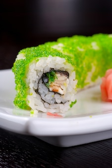 Sushi rolls made of salmon, avocado, flying fish roe - tobiko caviar and philadelphia cheese