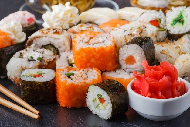 巻き寿司、巻き、握りセットは、暗い背景に黒い石のスレートに2つ提供しています