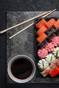 Суши-роллы на темном каменном фоне с бамбуковыми палочками и соевым соусом