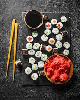 Суши-роллы на каменной доске с соевым соусом и имбирем. на темной деревенской поверхности