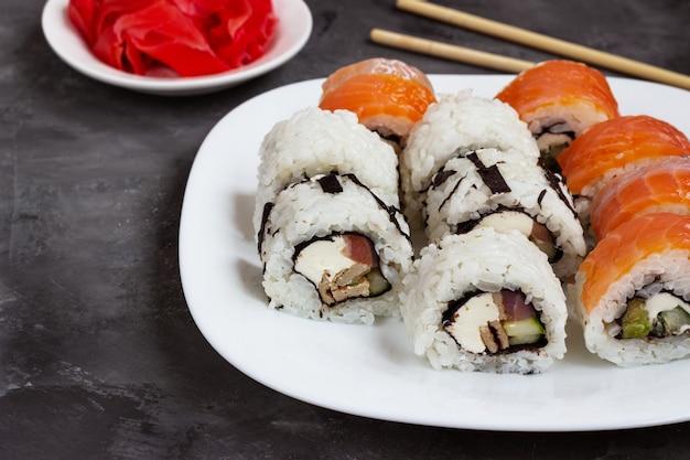 절인 생강과 검은 테이블에 흰색 접시에 스시 롤.