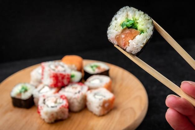 검은 배경에 스시 롤입니다. 일본 음식.
