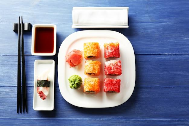 皿に巻き寿司、色の木製スペースに醤油と箸