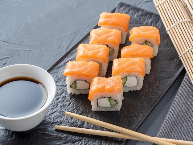 寿司は灰色の背景に黒い織り目加工のプレートスタンドにフィラデルフィアをロールバックします。わさび生姜とソース箸。サーモン、クリームチーズ、アボカドと一緒にロールパン。側面図