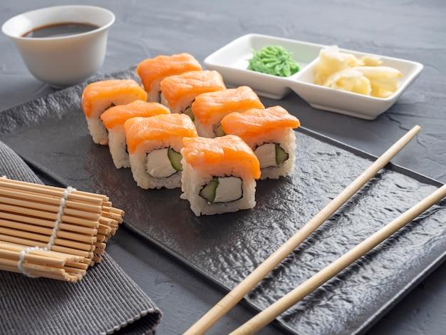 寿司は灰色の背景に黒い織り目加工のプレートスタンドにフィラデルフィアをロールバックします。わさび生姜とソース箸。サーモン、クリームチーズ、アボカドと一緒にロールパン。