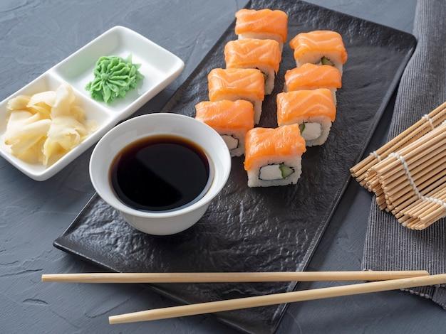 寿司は、灰色の背景に黒い織り目加工のプレートスタンドでフィラデルフィアをロールバックします。
