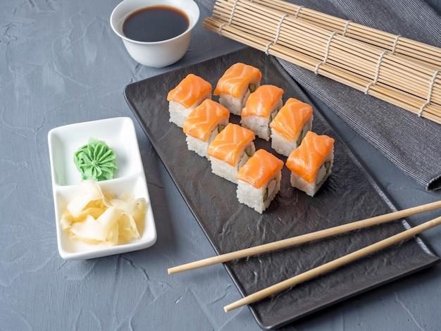 寿司は、灰色のテーブルわさび生姜とソース箸の上に黒いテクスチャプレートスタンドでフィラデルフィアをロールバックします。サーモン、クリームチーズ、アボカドと一緒にロールパン。