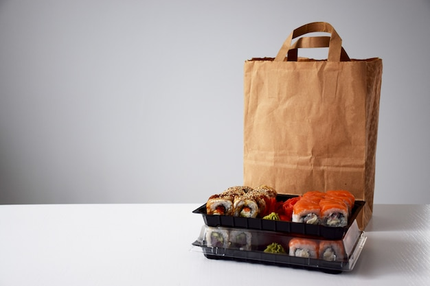 Sushi rolls in plastic box near paper package on white table. delivery or take away concept.