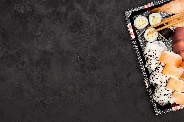 Sushi rolls and sashimi arranged on tray over textured floor
