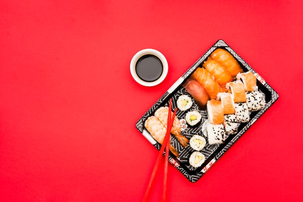 Sushi rolls and sashimi on tray with soy sauce over colored background