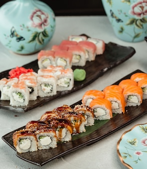 Sushi rolls selection in black plates.