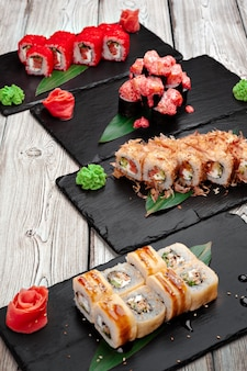 Sushi rolls served on boards on dark wooden background