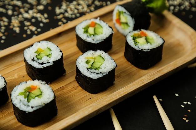 Суши роллы подаются на деревянной тарелке с классическими ингредиентами крупным планом