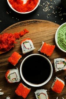 Суши роллы подаются на деревянной тарелке с классическими ингредиентами сверху