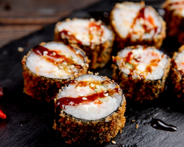 Sushi rolls served with sauce and sesame seeds