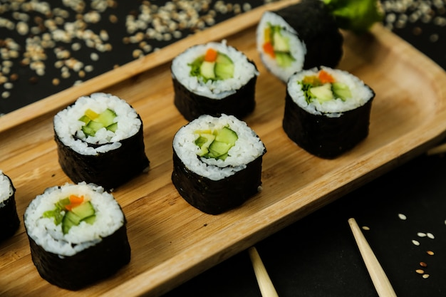 Sushi rolls served on wooden plate with classic ingredients close-up view