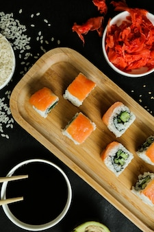 Sushi rolls served on wooden plate with classic ingredients top view
