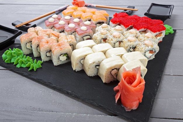 Sushi rolls set served on slate on dark background