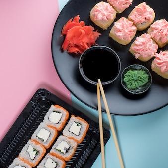 Суши роллы с соусом из красного майонеза и филадельфией на черной тарелке. розовый и синий стол. вид сверху. плоская планировка