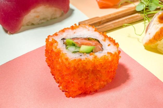 さまざまなカラフルな明るい背景、トレンディな暗い影のフラットレイにご飯と魚と箸をセットした巻き寿司